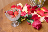 Red strawberry with petails of the roses — Stock Photo