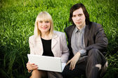 Business couple on the grass — Stock Photo