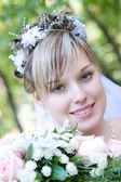 Bride with a flower bouquet by the tree — Stock Photo