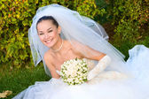 Happy bride with a flower bouquet in her hands — Stockfoto
