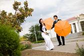 Bruden och brudgummen med orange paraplyer — Stockfoto