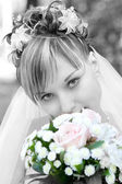 Shy bride with a flower bouquet — Stock Photo