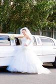 长长的白色婚礼在汽车附近的新娘 — 图库照片