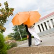 Stock Photo: Bride and groom with orange umbrellas