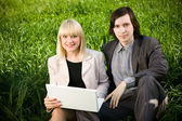 A couple working on laptop in nature on the grass field — Stock Photo