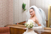 Young bride and big mirror — Stock Photo