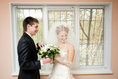 Braut und bräutigam mit blumen — Stockfoto