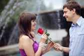 Man giving rose to a girl — Stock Photo