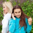 Mom and daughter talking by phones — Stock Photo #47349443