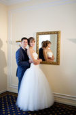 Bride and groom by the mirrir — Stock Photo