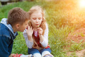 Girl and boy blow on dandelion — Stock Photo