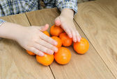 Hands of a boy with oranges — Stock Photo