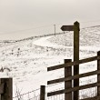 Blank wooden signpost on snow covered moorland — Stock Photo