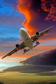 Passenger jet against a stormy sunset sky — Stock Photo