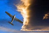 Small airplane against a stormy sunset sky — Stock Photo