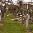 Rows of broken tombstones in a graveyard - Stock Photo