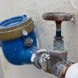 Stock Photo: Rusting old water valve with water meter
