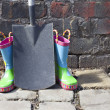 Royalty-Free Stock Photo: Childs wellington boots and shovel against an old brick wall