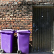 Rufuse bins against old brick wall - Stock Photo