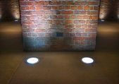 Interior brick wall lit up by spotlights — Stock fotografie