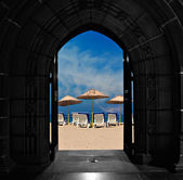 Looking through doors towards blue sky beach — Stock Photo