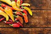Assortment of chilli peppers on a rustic wooden table — Stock Photo