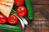 Tomatoes, cucumber, bread and spring onions on old wooden table — Stock Photo
