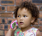 Young black baby girl talking on a toy cell phone — Stock Photo