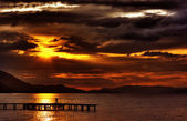 Hdr sunset with dramatic clouds and pier — Stock Photo