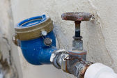 Rusting old water valve with water meter — Stock Photo