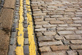 Modern (no parking) double yellow lines along ancient cobble stones — Stock Photo
