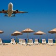 Jet flying over sunloungers on an empty beach — Stock Photo