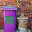 Wheelie bin and garden incinerator against brick wall - Stock Photo