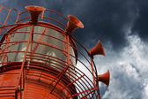 Bright red lighthouse with fog horns on white background — Stock Photo