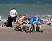 Pensioners sitting on deckchairs at British seaside resort — Stock Photo