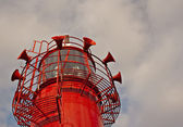 Bright red lighthouse with fog horns — Stock Photo