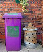 Wheelie bin and garden incinerator against brick wall — Stock Photo