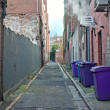 Rubbish bins lined up in narrow cobblestoned alley - Stock Photo