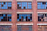 Broken windows on old derelict building — Stock Photo
