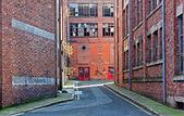 Looking down alleyway towards derelict building — Stock Photo