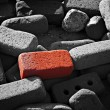 Single red brick amongst lots of monochrome bricks — Stock Photo