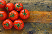 Fresh ripe tomatoes on a rustic wooden table — Stock Photo
