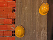 Construction workers yellow hard hats hanging on concrete wall — Stock Photo