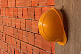 Construction workers yellow hard hat hanging on concrete wall — Stock Photo