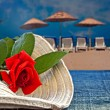 Stock Photo: Womans summer hat with red rose with empty beach