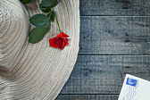 Womans summer hat with red rose and postcard — Stock Photo