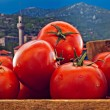 Box of red ripe tomatoes with old countryside background — Stock Photo