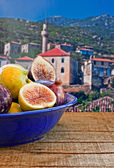 Bowl of fresh figs on rustic wooden table against village backgr — Stock Photo