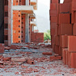 Stock Photo: Stack of red building blocks on messy site