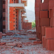 Stack of red building blocks on messy site — Stock Photo